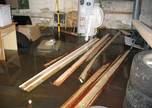 A severely flooding basement in Gresham, with lumber and personal items floating in a foot of water