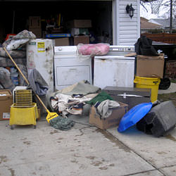 Soaked, wet personal items sitting in a driveway, including a washer and dryer in Hillsboro.