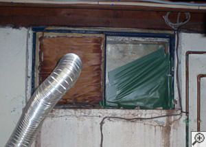 A basement window system that's rotted and  has been damaged over time in Woodburn.