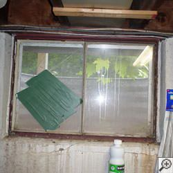 An old, rusted basement window with a steel frame in Hillsboro.